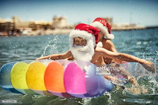 kids splashing on air bed during summer christmas - southern hemisphere stock photos and pictures