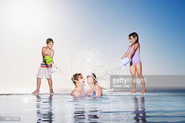 Niños jugando en los padres de agua en la piscina de borde infinito