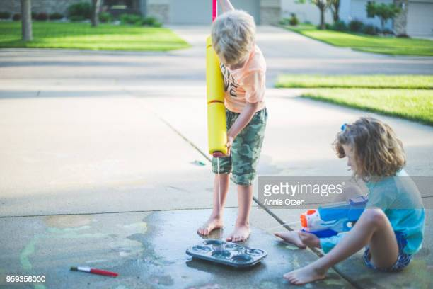 Kids squirt squirt guns into a cupcake tin