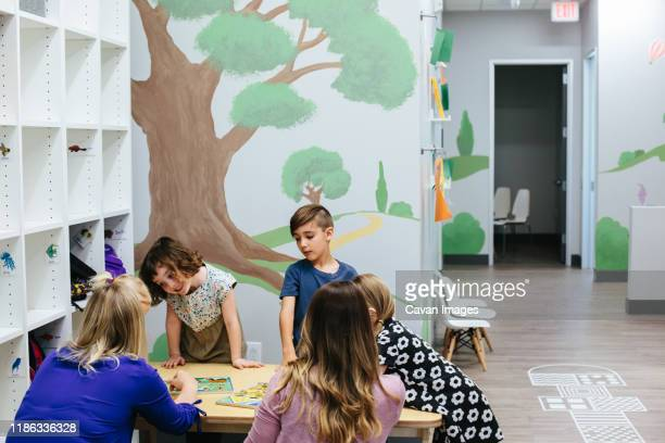 kids stand around a table with teachers and puzzles - calabasas stock pictures, royalty-free photos & images