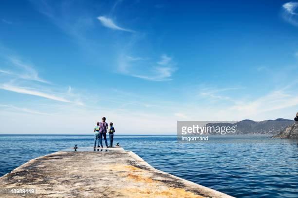 miúdos que estão no porto velho de corniglia, cinque terre, italy - céu claro - fotografias e filmes do acervo