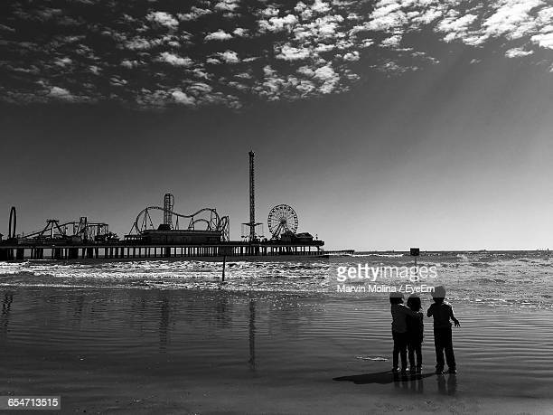 kids standing on shore at beach with galveston island historic pleasure pier against sky - galveston stock pictures, royalty-free photos & images
