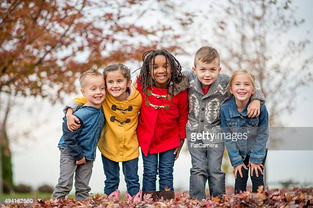 kids standing together in a row at the park - autumn falls stock pictures, royalty-free photos & images