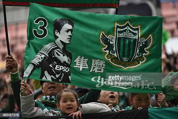 Kids supporters of Matsumoto Yamaga hold the flag of Hayuma Tanaka of Matsumoto Yamaga during the J. League match between Nagoya Grampus and...