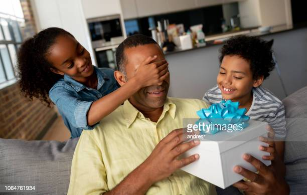 Kids surprising their father with a gift for Father's Day