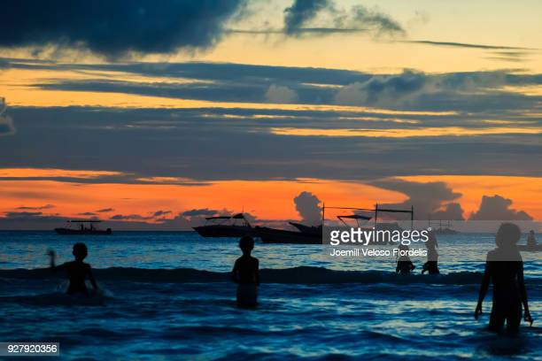 Kids swimming at sunset in Boracay Island (Malay, Aklan, Philippines)