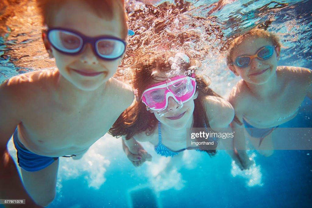 Kids swimming underwater : Stock Photo
