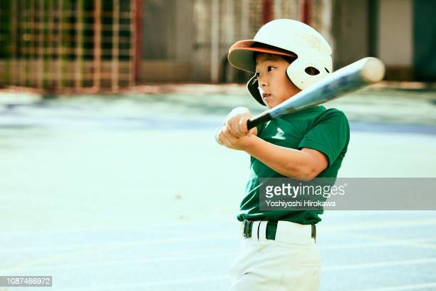 kids (8-9) swinging baseball bat at ball - batting sports activity stock pictures, royalty-free photos & images