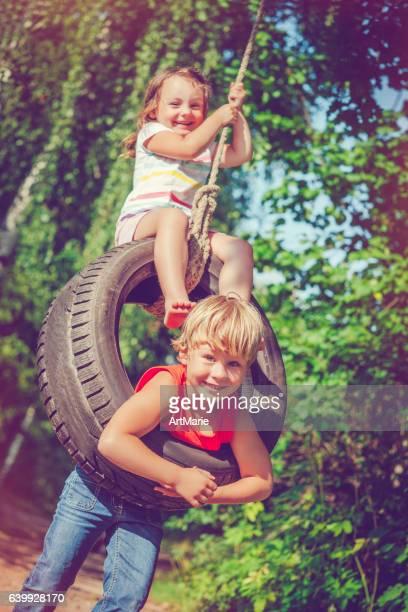 Kids swinging in summer
