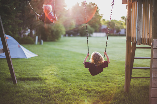 Kids swinging on swing set - gettyimageskorea