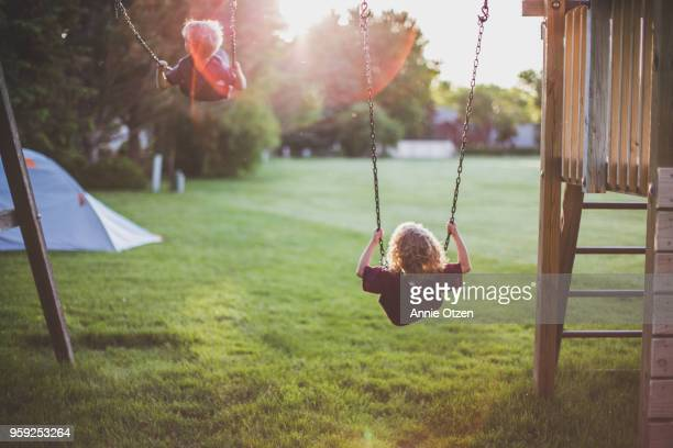 kids swinging on swing set - real life stock pictures, royalty-free photos & images