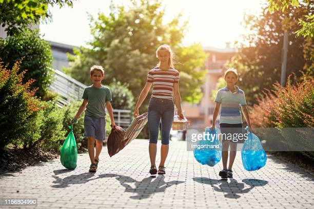 kids taking out the segregated garbage - absence stock pictures, royalty-free photos & images