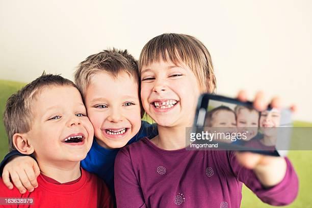 kinder nehmen foto mit handy - video call stock-fotos und bilder