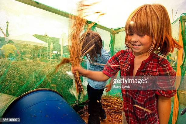 Kids threashing wheat at Brockwell Bake's mobile bakery on Southwark Bridge which is transformed into a giant banqueting space designed by Cathy Wren...