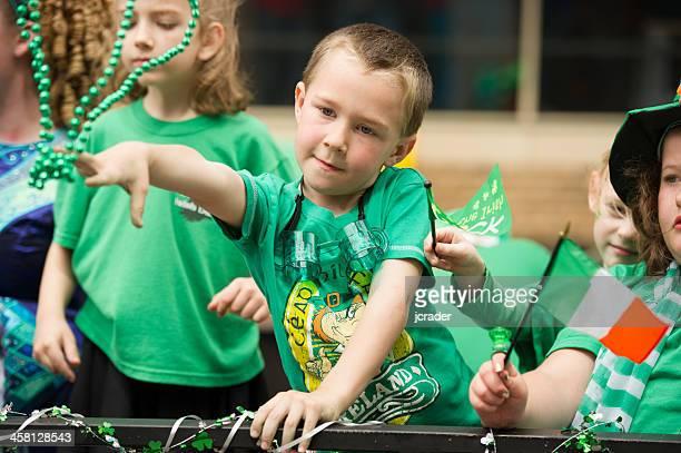 Kinder werfen Perlen an den St. Patrick's Day Parade Besucher