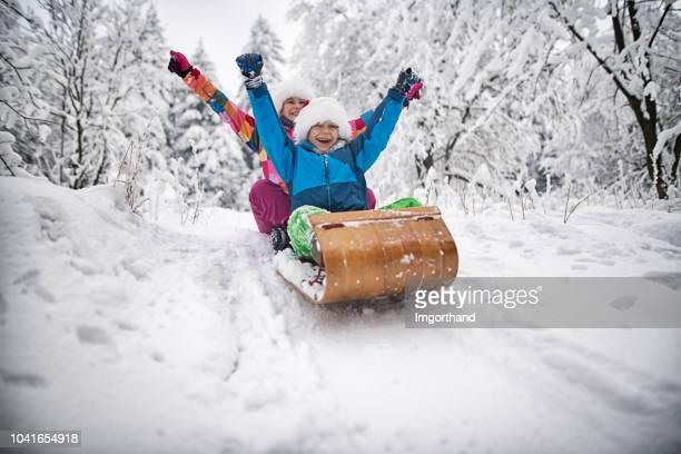niños trineo en navidad - deporte de invierno fotografías e imágenes de stock