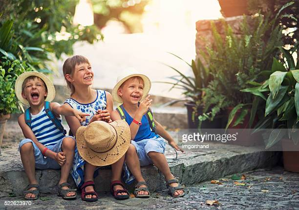 Kids tourist laughing in mediterranean street.