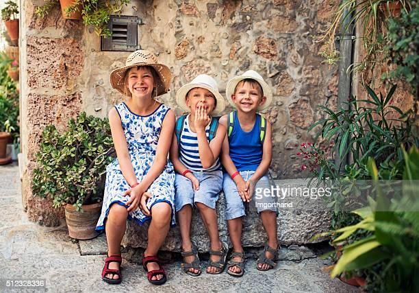 Kids tourist resting in mediterranean street.