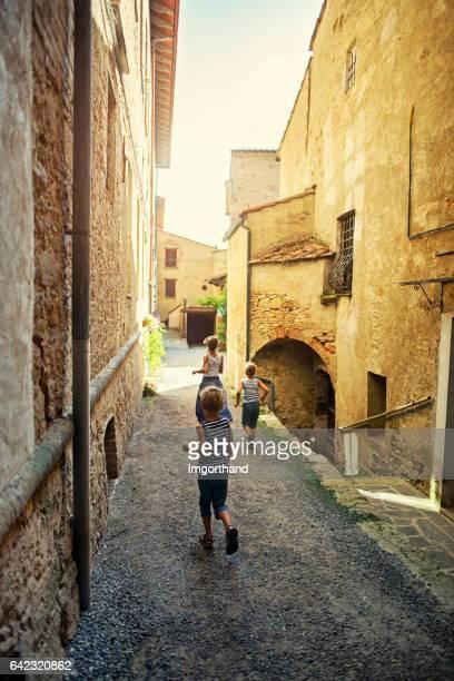Les enfants touristiques en cours d'exécution à l'arrière rue de Volterra, Toscane, Italie