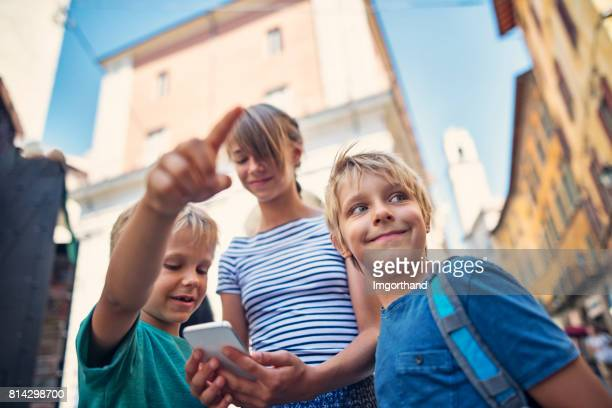 Kids tourists checking directions on smartphone