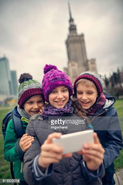 Kids tourists making funny selfie at Warsaw, Poland