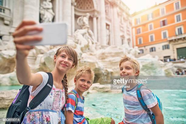 Kids tourists making selfie at Trevi Fountain, Rome