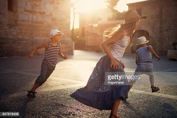 Kids tourists playing tag in mediterranean street.