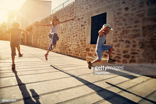 Kids tourists running and jumping in mediterranean street.