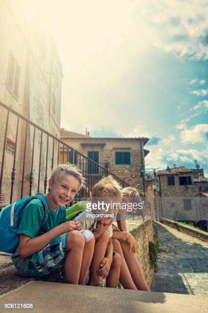 Kids tourists sightseeing beautiful italian town in Tuscany