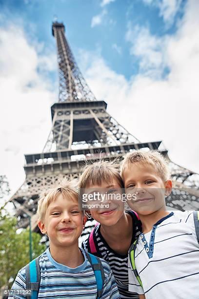 Kinder Touristen, lächelt in die Kamera, in der Nähe von Eiffelturm