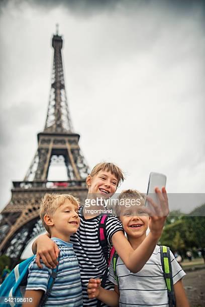 Kinder Touristen nehmen selfie nahe dem Eiffelturm