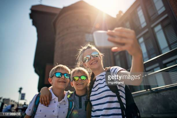 kids tourists taking selfies near the old port crane in gdansk, poland - monument stock pictures, royalty-free photos & images