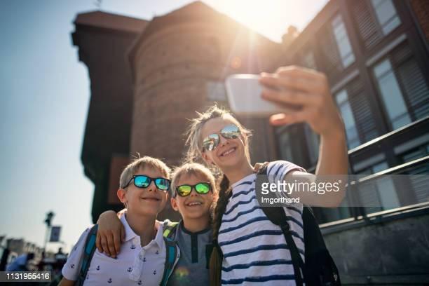 kids toeristen nemen selfies in de buurt van de oude havenkraan in gdansk, polen - monument stockfoto's en -beelden