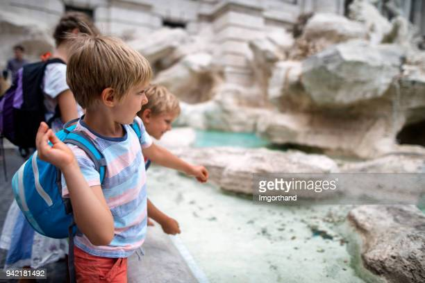 kids tourists throwing coins into trevi fountain, rome - luck stock pictures, royalty-free photos & images
