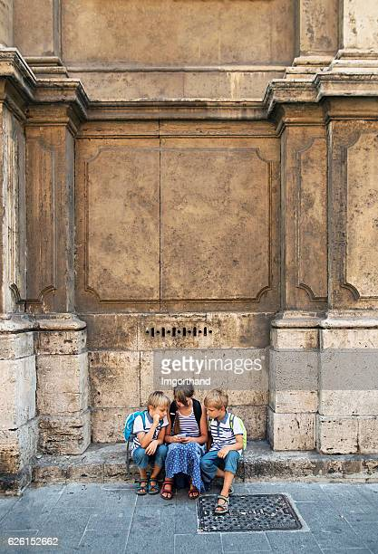 Kids tourists using smartphone near church in Rome