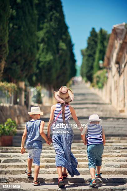 Kids tourists walking on famous stairs in beautiful majorcan city of Pollensa