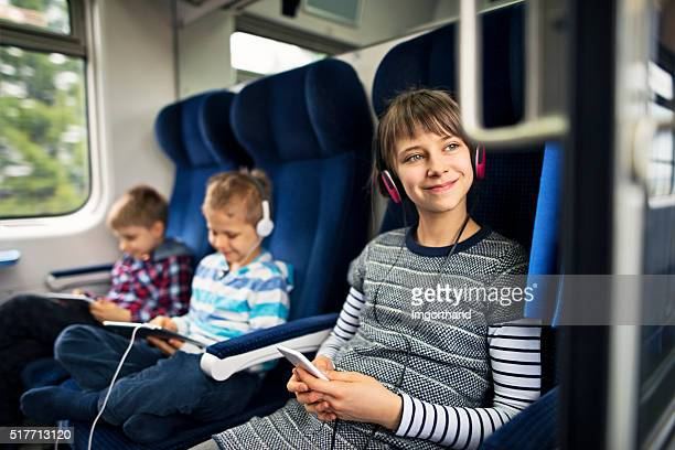 Kids travelling on train playing tablets and listening to music