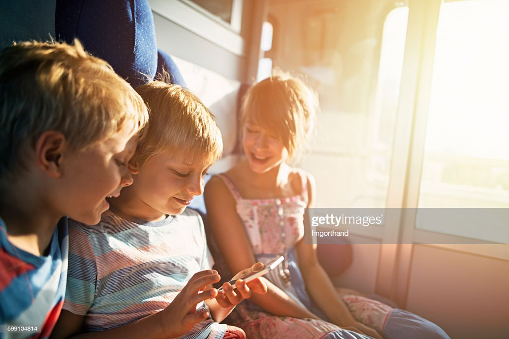 Kids travelling on train playing with smartphone : Stock-Foto