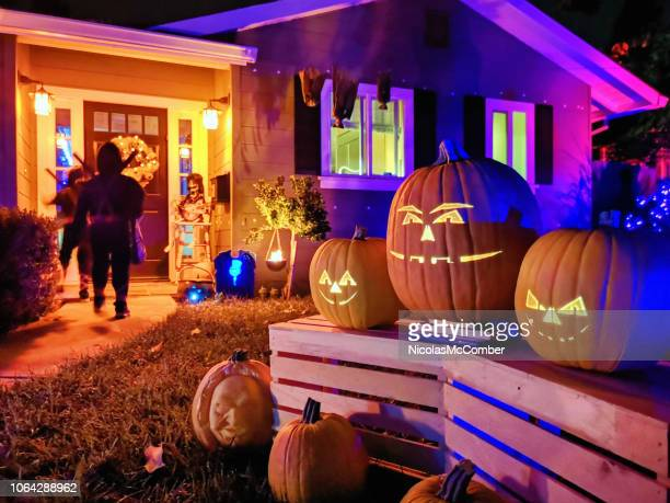 kids trick or treating on halloween night in suburban californian house - halloween decoration stock pictures, royalty-free photos & images