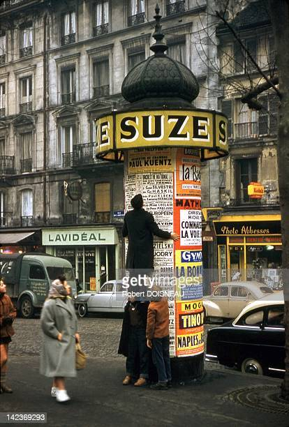 Kids trying to climb onto a Morris column Paris France in 1957
