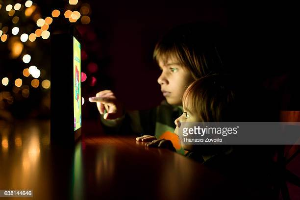 Kids using a digital tablet in the dark