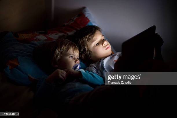 Kids using a dogital tablet in the dark