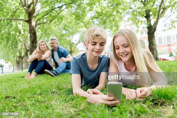 Kids using cell phone at the park