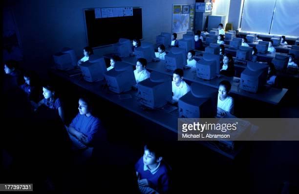 Kids using computers in a dark room at school undated