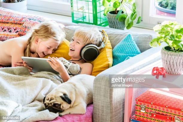 Kids using digital tablet on sofa