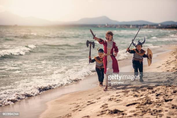 Kids vikings charging thrrough the beach