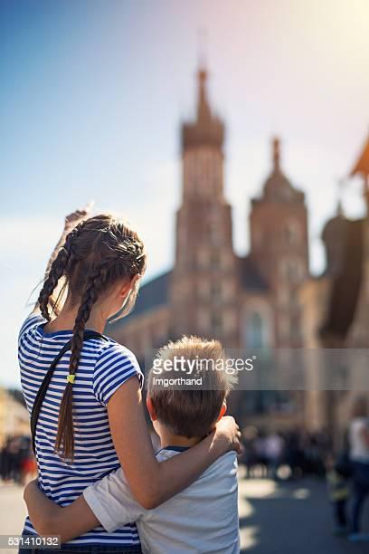 Kids visiting Krakow and looking at Mariacki Church (St. Mary)