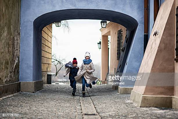Kids visiting Warsaw -  running in old town back street