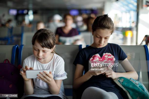 kids waiting at the airport and playing with mobile phones - mood stream stock pictures, royalty-free photos & images