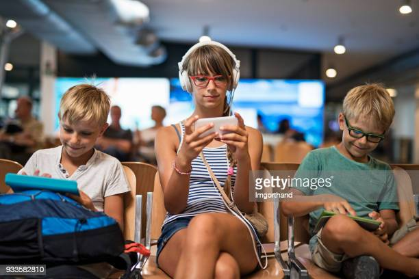 Kids waiting at the airport and playing with smart devices